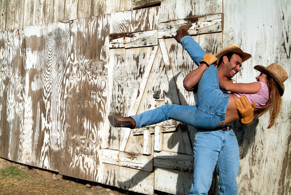 Cowboy and wife playing around outside of barn in San Diego, California, USA, North America