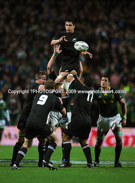All Blacks lock Isaac Ross pops lineout ball down to Jimmy Cowan as Pierre Spies (right) looks on.<br /> Investec Tri-Nations rugby match - All Blacks v Springboks at Waikato Stadium, Hamilton, New Zealand on Saturday 12 September 2009. Photo: Dave Lintott/PHOTOSPORT