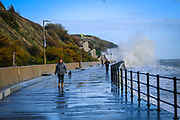 People walk along the wet walkway while sea waves crash over the path behind on Sunny Sunny Sands Beach, Folkestone, Kent, UK. It is high tide and the beach is completely covered by the sea which is rough and choppy due to stormy weather.  (photo by Andrew Aitchison / In pictures via Getty Images)
