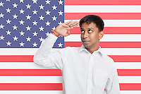 Young Asian man in shirt saluting against American flag