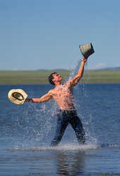 Man in a lake pouring water on himself with a bucket