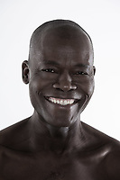 studio shot portrait of a bare smiling forty Handsome Afro-American Man
