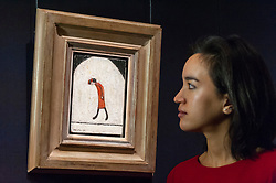 "© Licensed to London News Pictures. 18/11/2016. London, UK. A staff member views ""Woman in Red"" by Laurence Stephen Lowry (est. GBP60-80k), at the preview at Sotheby's of works on view at four upcoming November auctions featuring Modern & Post-War British Art, A Painter's Paradise (Julian Trevelyan & Mary Fedden at Durham Wharf), Scottish Art and Picasso Ceramics from the Lord & Lady Attenborough Private Collection. Photo credit : Stephen Chung/LNP"