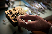 Billy Beguelin shows the working mechanism of a clock he is working on. Image © Angelos Giotopoulos/Falcon Photo Agency