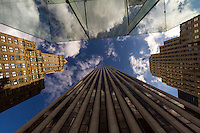 A straight up view from downtown New York City into the blue, cloudy sky above.
