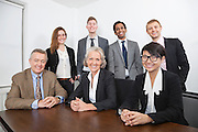 Portrait of happy multiethnic business group at desk in office