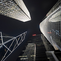 Asia, Peoples Republic of China, Hong Kong, View looking up at Bank of China building and surrounding office towers in city's Central financial district at night
