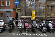 Scooters and motorcycles are left parallel in their specific parking bay with a parking suspension warning sign in Wardour Street, Soho, on 16th April 2018, in London, England.