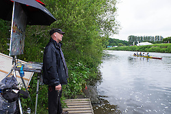 © Licensed to London News Pictures.13/06/15<br /> Durham, England<br /> <br /> An artist turns from his work to watch the rowing during the 182nd Durham Regatta rowing event held on the River Wear. The origins of the regatta date back  to commemorations marking victory at the Battle of Waterloo in 1815. This is the second oldest event of this type in the country and attracts over 2000 competitors from across the country.<br /> <br /> Photo credit : Ian Forsyth/LNP
