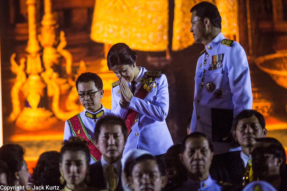 YINGLUCK SHINAWATRA (center) the Prime Minister of Thailand, and ANUSORN AMORNCHAT, her husband, (right) enter the celebration of the birthday of the King in Bangkok. Thais observed the 86th birthday of Bhumibol Adulyadej, the King of Thailand, their revered King on Thursday. They held candlelight services throughout the country. The political protests that have gripped Bangkok were on hold for the day, although protestors did hold their own observances of the holiday. Thousands of people attended the government celebration of the day on Sanam Luang, the large public space next to the Grand Palace in Bangkok.