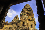 """02 JULY 2013 - ANGKOR WAT, SIEM REAP, SIEM REAP, CAMBODIA:  Angkor Wat  scene through a window in the temple. Angkor Wat is the largest temple complex in the world. The temple was built by the Khmer King Suryavarman II in the early 12th century in Yasodharapura (present-day Angkor), the capital of the Khmer Empire, as his state temple and eventual mausoleum. Angkor Wat was dedicated to Vishnu. It is the best-preserved temple at the site, and has remained a religious centre since its foundation– first Hindu, then Buddhist. The temple is at the top of the high classical style of Khmer architecture. It is a symbol of Cambodia, appearing on the national flag, and it is the country's prime attraction for visitors. The temple is admired for the architecture, the extensive bas-reliefs, and for the numerous devatas adorning its walls. The modern name, Angkor Wat, means """"Temple City"""" or """"City of Temples"""" in Khmer; Angkor, meaning """"city"""" or """"capital city"""", is a vernacular form of the word nokor, which comes from the Sanskrit word nagara. Wat is the Khmer word for """"temple grounds"""", derived from the Pali word """"vatta."""" Prior to this time the temple was known as Preah Pisnulok, after the posthumous title of its founder. It is also the name of complex of temples, which includes Bayon and Preah Khan, in the vicinity. It is by far the most visited tourist attraction in Cambodia. More than half of all tourists to Cambodia visit Angkor.         PHOTO BY JACK KURTZ"""