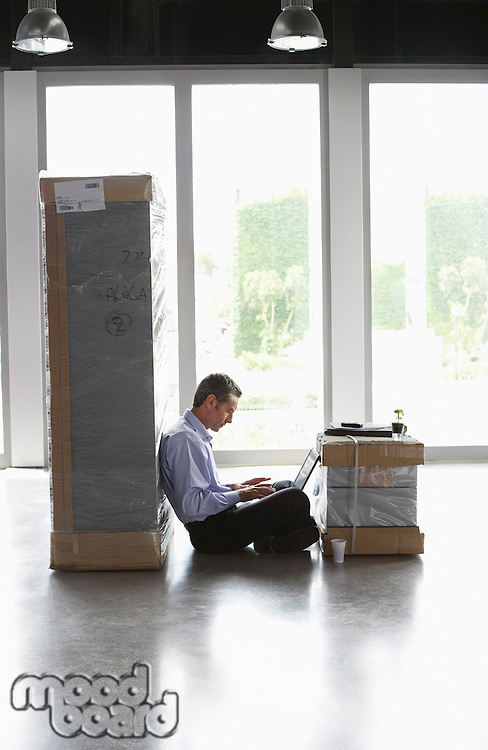 Man using laptop between packages in empty office