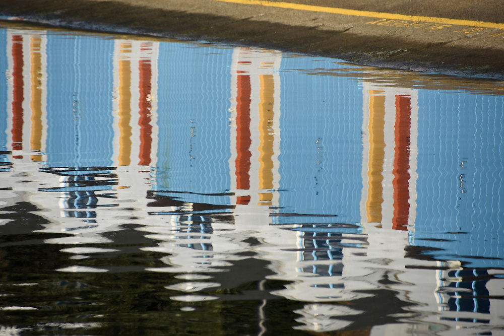 Refection of the houses and beach huts at a marina in Wellington