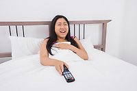 Happy woman watching TV in bed