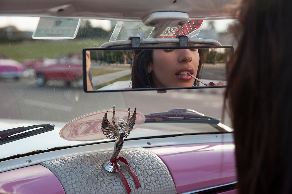 A young woman retouches her lipstick make-up on the rearview mirror of and old American convertible in Havana, Cuba.