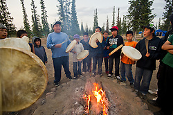 """First Nation Dene youth beat drums near a fire during a spiritual gethering in Reliance after a group returns on a canoe trip from the Upper Thelon River is """"the place where God began.""""  Sparsely populated, today few make it into the Thelon. Distances are simply too far, modern vehicles too expensive and unreliable. For the Dene youth, faced with the pressures of a western world, the ties that bind the people and their way of life to the land are even more tenuous. Every impending mine, road, and dam construction threatens to sever these connections. In July and August, 2011 a group of youth paddled to their ancestral hunting ground and spiritual abode.  this next generation of young leaders will be the ones who will need to speak for the Thelon the loudest. (Photo by Ami Vitale)"""