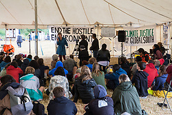 Roydon, Essex, UK. 27 July, 2019. Activists listen to a talk on the 'Theft of Africa' in the Main Marquee at Reclaim The Power's Power Beyond Borders mass action camp.