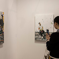 Visitor takes photo of artist Raffi Kalenderian's 'Jaques, 2017' (L) and 'Self Portrait in the Studio, 2017' (R) at Art Basel Hong Kong 2017 on 23 March 2017, in Hong Kong Convention and Exhibition Centre, Hong Kong, China. Photo by Chris Wong / studioEAST