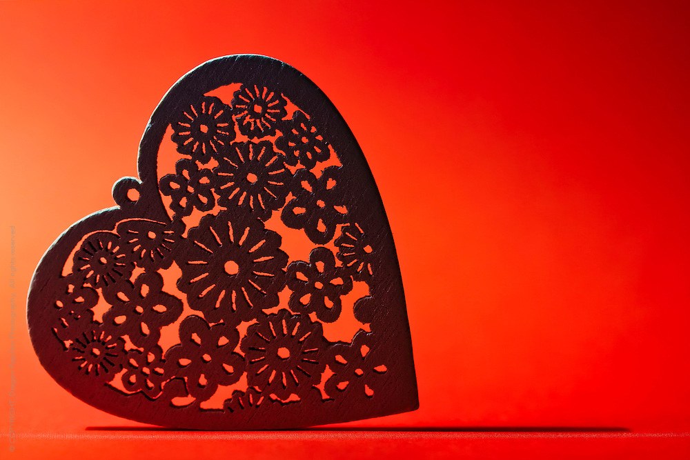 carved wooden heart against orange red background with underlining shadow