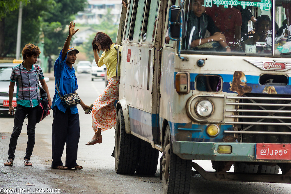 19 JUNE 2013 - YANGON, MYANMAR:  A conductor signals to a bus driver to wait as passengers step off the bus. Yangon buses are generally overcrowded and in poor repair but as the economy improves newer, but still used, Japanese and Korean buses are being imported. Hundreds of bus routes criss-cross Yangon, providing the cheapest way of getting around the city. Most fares are less than the equivalent of .20¢ US.  PHOTO BY JACK KURTZ