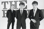 Three young men in the band The Bishops standing in front of wall with their band name written in capital letters.