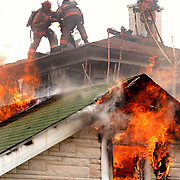 Syracuse, NY / 2003 - The Syracuse fire department battled a blaze that began at 1008 Park Street and spread to the adjacent building at 1012 Park Street on April 13, 2003.  In an attempt to put out the fires, firemen are chopping a ventilation hole in the roof of 1012 Park Street.  The fire was called in at approximately 2:30pm. Photo by Mike Roy