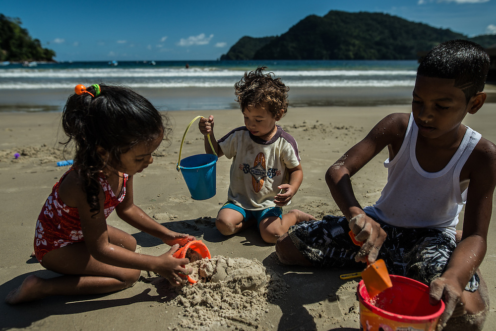 MARACAS BAY, TRINIDAD - FEBRUARY 14, 2017: Toria Dhanookdharry, 3, (left) Lucah Chin, 2, (Center) and Isaiah Mercano, 10, build sandcastles on the beach at Maracas Bay, the most popular beach within reach of the capital where crowds of people flock to go swimming in the clean, warm sea backed by lush green hills.  PHOTO: Meridith Kohut for The New York Times
