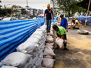 """30 DECEMBER 2013 - BANGKOK, THAILAND: Anti-government protestors put sandbags across Ratchadamnoen Road in Bangkok. Violence around the anti-government protest sites has escalated in recent days and several protestors have been hurt by small explosive devices thrown at their guard posts. As a result, protestors are fortifying their positions with sandbags and bunkers. Suthep Thaugsuban, the leader of the anti-government protests in Bangkok, has called for a new series of massive protests after the 1st of the year and said it the shutdown, or what he described was the seizure of the capital, would be the day when """"People's Revolution"""" would """"begin to end and uproot the Thaksin regime.""""          PHOTO BY JACK KURTZ"""