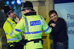"© Licensed to London News Pictures . 19/12/2014 . Manchester , UK . Police handcuff and detain a man outside TGI Fridays in Manchester City Centre . "" Mad Friday "" revellers out in the rain and cold in Manchester . Mad Friday is typically the busiest day of the year for emergency services , taking place on the last Friday before Christmas when office Christmas parties and Christmas revellers enjoy a night out .  Photo credit : Joel Goodman/LNP"