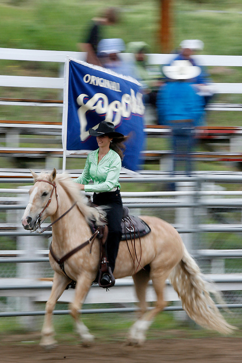 062009-Evergreen, Colo.-queenshc-2010 Evergreen Rodeo Queen Kari Peterson rides through the arean as the rain pours down during the 2009 Evergreen Rodeo Queens Horsemanship Competition Saturday, June 20, 2009 at The Evergreen Rodeo Grounds..Photo By Matthew Jonas/Evergreen Newspapers/Photo Editor
