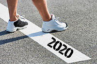 Man standing on stepping on white line with year 2020 sign