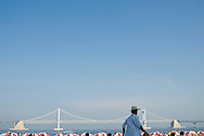 A man passes in front of a sea of red and white beach umbrellas and the Gwangan Bridge, Busan, South Korea.