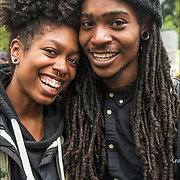 Smiling young African American couple, female with facial piercings and nose ring and male with dreadlocks, in Union Square Park after the Cannabis Parade