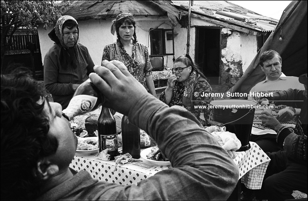 NANICA LUMINITA STANESCU, 2ND FROM LEFT STANDING,CELEBRATING EASTER WITH HER ROMANIAN NON-GYPSY NEIGHBOURS. ROMANIAN ORTHODOX EASTER CELEBRATIONS. SINTESTI, ROMANIA, EASTER 1995..©JEREMY SUTTON-HIBBERT 2000..TEL./FAX. +44-141-649-2912..TEL. +44-7831-138817.