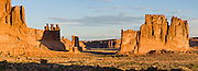 The orange sandstone Courthouse Towers resist erosion in Arches National Park, Utah, USA. These rock monuments are beautiful both at sunrise (seen here) and sunset. At left are the Three Gossips. The Courthouse Towers are comprised of the Slick Rock member of Entrada Sandstone above the red-brown. or chocolate-brown marker beds of the Dewey .Bridge member. (Panorama stitched from 3 photos.)