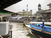 21 NOVEMBER 2012 - BANGKOK, THAILAND:  A passenger boat on Khlong Saen Saeb passes a mosque in a Muslim section of Bangkok. Bangkok used to be criss crossed by canals (called Khlongs in Thai) but most have been filled in and paved over. Khlong Saen Saeb is one of the few remaining khlongs in Bangkok with regular passenger boat service. Khlong Saen Saeb was dug in 1837 to be a military supply line from Bangkok to Siamese armies battling Annamese (now Vietnamese) forces in what is now Cambodia. Boats and ships play an important in daily life in Bangkok. Thousands of people commute to work daily on the Chao Phraya Express Boats and fast boats that ply Khlong Saen Saeb. Boats are used to haul commodities through the city to deep water ports for export.   PHOTO BY JACK KURTZ