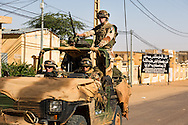 French troops patrol past a sign in Timbuktu proclaiming the city is under Sharia law after taking the city back from Islamic militants on Jan. 30, 2013.