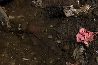 A child's doll lays stuck in filth behind a dwelling in Guatemala City's massive trash dump, where people over 14 years old are allowed to spend their days rummaging for recyclables.