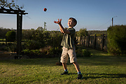 An 8 year-old boy plays catch in the back garden of a rural property, on 5th May 2018, in Wrington, North Somerset, England.
