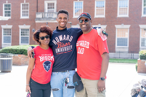 A smiling Howard University student with his parents, all wearing university merchandise.