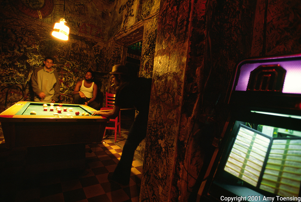 OLD SAN JUAN, PR - FEBRUARY 16: A group of men play billiards in El Batey, a 24 hour bar February 16, 2002 in Old San Juan, Puerto Rico. Puerto Rico was an outpost of Spanish colonialism for 400 years, until the United States took possession in 1898. Today Puerto Rico's Spanish-speaking culture reflects its history - a mix of African slaves, Spanish settlers, and Taino Indians. Puerto Ricans fight in the U.S. armed forces but are not entitled to vote in presidential elections. They passionately debate their relationship with the U.S. with about half the island wanting to become the 51st state and the other half wanting to remain a U.S. commonwealth. A small percentage feel the island should be an independent country. While locals grapple with the evils of a burgeoning drug trade and unchecked development, drumbeats still drive the rhythms of African-inspired bomba music. (Photo By Amy Toensing) _________________________________<br />