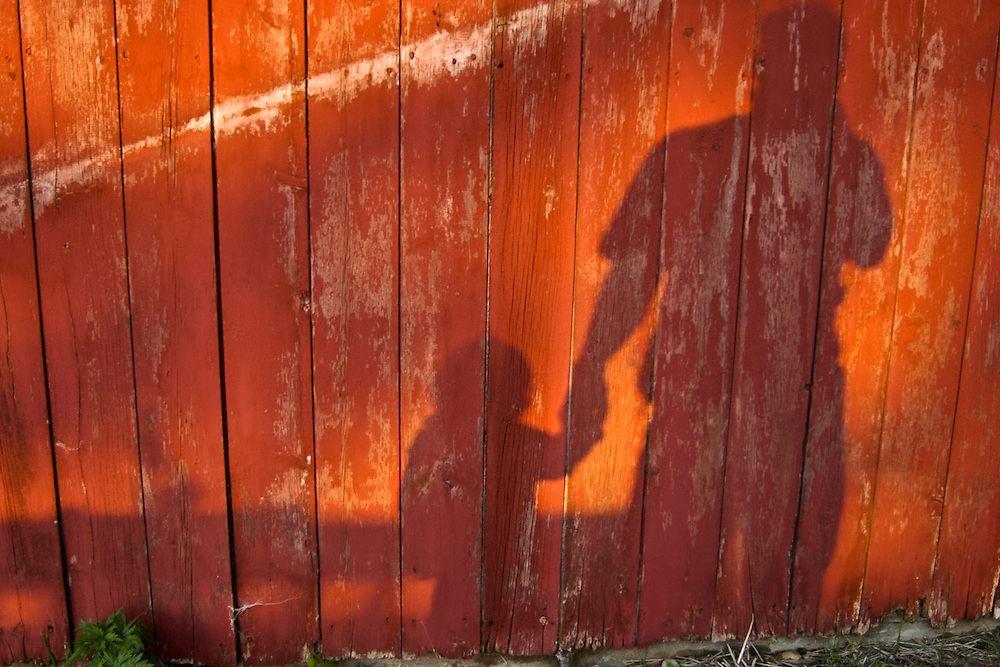 The shadow of photographer Jeff Miller and Rachel Stute, his almost-three-year-old niece, are cast upon the side of a red barn at the Stute family farm during sunset in East Troy, Wis., on May 13, 2003. On the 159-acre farm, Michele Stute raises more than 100 Clun Forest sheep and her husband Jim Stute tends to soybeans, corn, wheat and hay crops in addition to his full-time state position as an agricultural extension specialist.