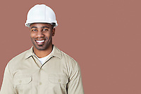 Portrait of happy young construction worker with hardhat over brown background