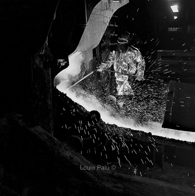 A furnace tapper using a thermal lance to test the purity of molten nickel in the furnace, which operates at over 1000 degrees Celsius at the Falconbridge Smelter, Falconbridge, Ontario. From the book Cage Call: Life and Death in the Hard Rock Mining Belt. An in-depth project spanning over 12-years examining communities in one of the richest mining regions in the world located in Northwestern Ontario and Northeastern Quebec in Canada.