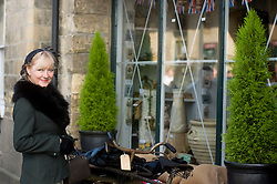 A reenactor, from the Northern World War Two Association, dressed in civilian clothing beside a shop window which has been dressed up to reflect the feel of the Pickering 1940s war weekend 16th-18th October 2009 Image Copyright Paul David Drabble