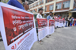 July 24, 2017 - Kathmandu, NP, Nepal - Supporters hold placards with a written message, WE ARE WITH DR. GKC during 11th time hunger strike  demanding Integrated Medical Education act at Teaching Hospital in Kathmandu on Monday, July 24, 2017. (Credit Image: © Narayan Maharjan/NurPhoto via ZUMA Press)