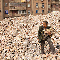 China, Xi'an, Elderly Chinese man collects wood scraps at site of demolished apartment building