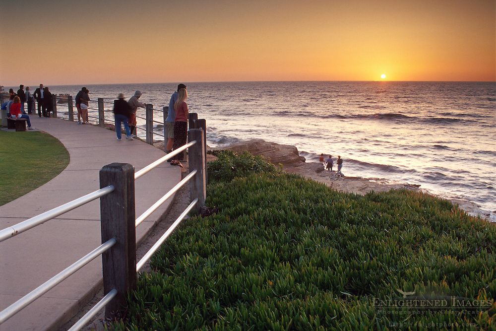 tourists watch the sunset over the Pacific Ocean from sidewalk above coastal cliffs at Scripps Park, La Jolla, San Diego County, California