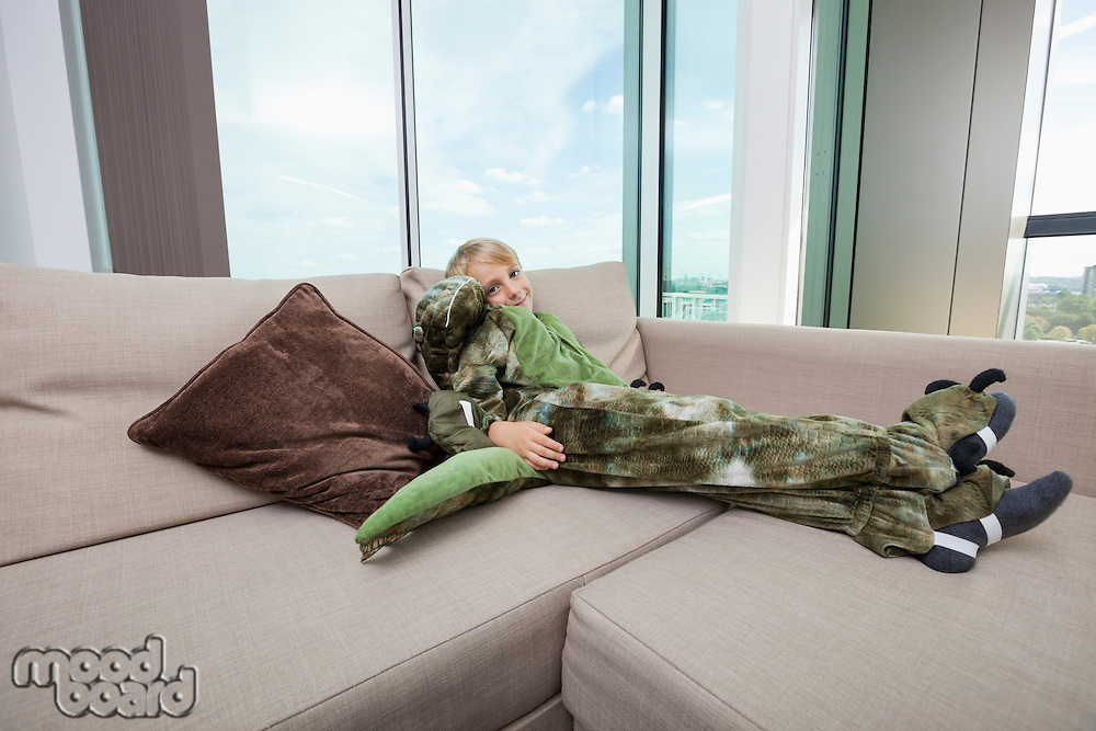 Portrait of boy wearing dinosaur costume relaxing on sofa at home