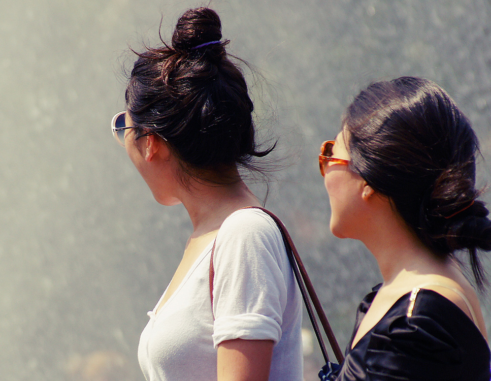 Color shot of 2 pretty Asian girls wearing sunglasses walking by fountain in Washington square park NYC 2010